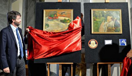 Italy's culture minister Dario Franceschini unveils the rediscovered paintings, Paul Gauguin's Fruits sur une table, left, and Pierre Bonnard's La femme aux deux fauteuils. Photograph: Andreas Solaro/AFP/Getty Images