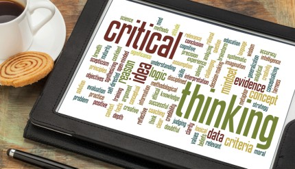 critical thinking word cloud on a digital tablet with a cup of coffee