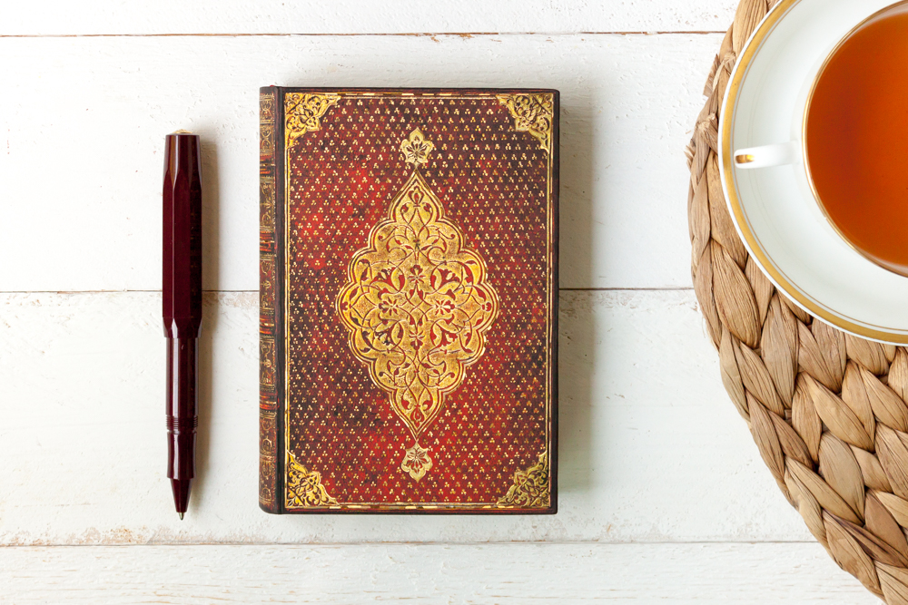 Paperblanks Golden Trefoil journal on a table with pen and tea.