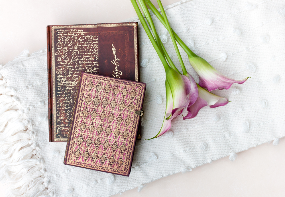 Paperblanks Shakespeare, Sir Thomas More and River Cascade Alluvium journals with pink flowers on a white blanket.